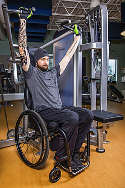 A paraplegic man working out using an overhead press in fitness facility; Sherwood Park, Alberta, Canada