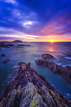 Sunrise along the Irish coast with rock formations in the foreground and Ballycotton lighthouse on the horizon; Ballycotton, County Cork, Ireland
