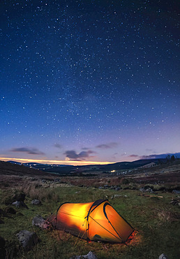 A lit up tent pitched in the Wicklow Mountains at night with stars in the sky; County Wicklow, Ireland
