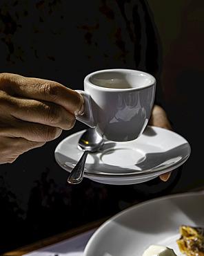 Espresso coffee being held against a dark background; Melbourne, Victoria, Australia