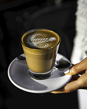 Cafe Latte with coffee art design being held by a woman's hand; Melbourne, Victoria, Australia