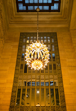 Illuminated and decorative round chandelier hanging in front of a mirror in a Manhattan building; New York City, New York, United States of America