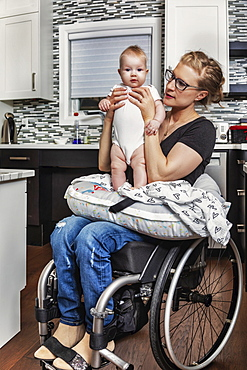 A paraplegic mother holding her baby on her lap, in her kitchen, while sitting in her wheel chair: Edmonton, Alberta, Canada