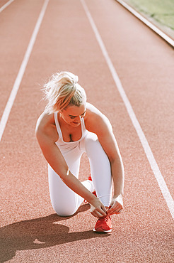 Woman kneels to tie her running shoe to prepare for running on a track; Wellington, New Zealand