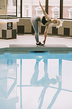 Woman working out on a mat beside a pool; Wellington, New Zealand