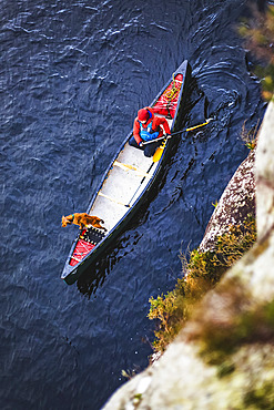 High angle view of woman and dog paddling a canoe on a lake in Ireland in winter, Killarney National Park; County Kerry, Ireland