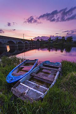 Two old wooden boats on the banks of the Shannon River at sunset with a stone bridge in the background; Montpellier, County Limerick, Ireland