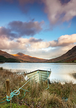 A boat on a lake shoreline with a valley and mountains in the background; Black Valley, County Kerry, Ireland