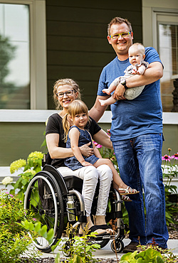 A young family posing for a family portrait outdoors in their front yard and the mother is a paraplegic in a wheelchair; Edmonton, Alberta, Canada