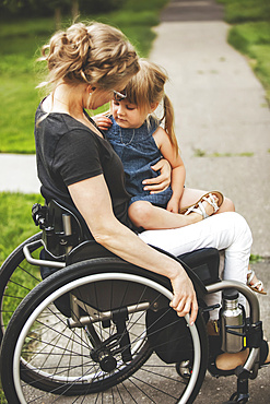 A paraplegic mom holding her little girl in her lap while taking her for a ride down the street in her wheelchair on a warm summer afternoon: Edmonton, Alberta, Canada.