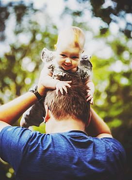 A father holding his baby girl in the air while outdoors during the fall; Edmonton, Alberta, Canada