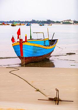 Colourful fishing boat tied to the beach, Ke Ga Cape; Ke Ga, Vietnam