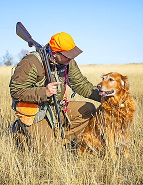 Hunter with rifle crouching beside a golden retriever dog; Denver, Colorado, United States of America