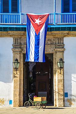 The national flag of Cuba hangs over the entrance to the Palace of the Artisans (Palacio de la Artesania), Old Town; Havana, Cuba