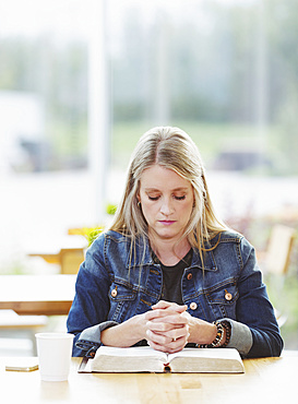 A mature woman praying, after doing some personal Bible study, in a coffee shop : Edmonton, Alberta, Canada