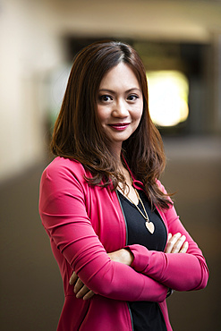A close-up portrait of an Asian business woman in a hallway at her place of work: Edmonton, Alberta, Canada
