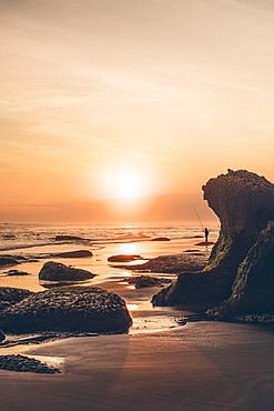 Sunset at Parangendog Beach with a person fishing from the beach; Purwosari, Yogyakarta, Indonesia