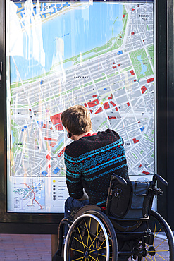 Man in a wheelchair looking at a map of a city posted on a wall