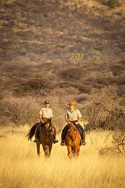 Two women riding horses (Equus ferus caballus) traveling through the grass near a hill at the Gabus Game Ranch at sunset; Otavi, Otjozondjupa, Namibia