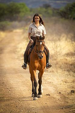 Woman riding horse (Equus ferus caballus) on a dirt road through the bush on the savanna looking at the camera and smiling at the Gabus Game Ranch; Otavi, Otjozondjupa, Namibia