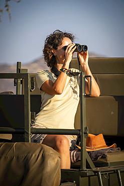 Woman sitting in sunlit jeep using binoculars on safari at the Gabus Game Ranch; Otavi, Otjozondjupa, Namibia