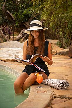 Woman wearing sunhat sitting by a swimming pool reading at the Gabus Game Ranch; Otavi, Otjozondjupa, Namibia