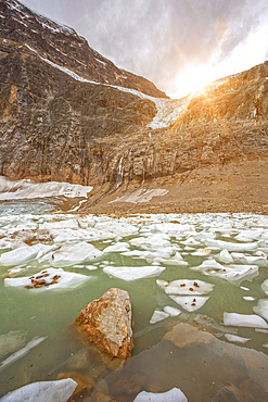 Ice chunks float in the glacial water of the Rocky Mountains with a sunburst shining bright over Mount Edith Cavell in Jasper National Park; Alberta, Canada