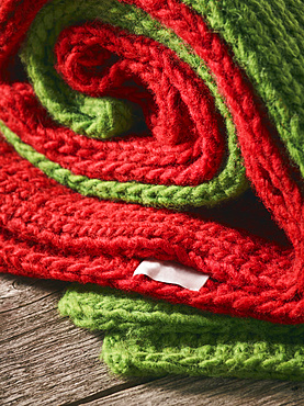 Close-up of a red and green knitted garments folded together and laying on a wooden table; Studio