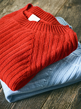Red and blue folded sweaters on display on a wooden table; Studio