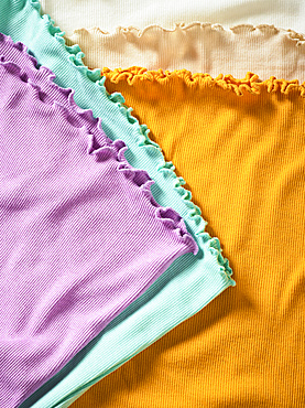 Colourful pieces of clothing with ruffled trim lay in a pile; Studio