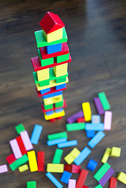 Colourful blocks stacked into a tower and dispersed on the floor at playtime; Surrey, British Columbia, Canada
