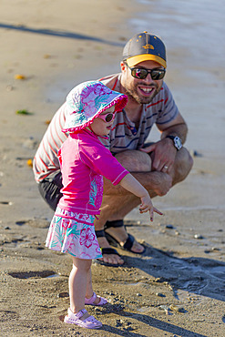 A father spends quality time with his toddler daughter at the water's edge at Ambleside Beach; West Vancouver, British Columbia, Canada