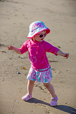 A toddler girl plays at the beach with sunglasses and sun hat, Ambleside Beach; West Vancouver, British Columbia, Canada
