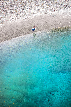 The Blue Pools of Makarora offer enticing blue waters to swim in. A woman crouches by the water's edge to take a picture with her camera, Mount Aspiring National Park; Makarora, Otago, New Zealand