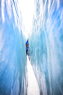A tight squeeze for travelers exploring New Zealand's famous Franz Josef Glacier, iwth its blue Ice, deep crevasses, caves and tunnels that mark the ever changing ice formations; West Coast, New Zealand