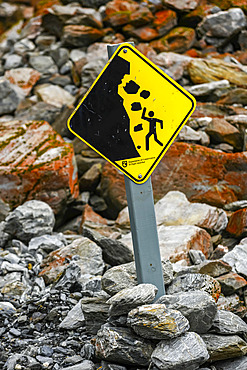 Cautionary sign placed on rocky trail to beware of falling rocks along the Franz Josef Glacier Walk in Westland Tai Poutini National Park; Whataroa, West Coast Region, South Island, New Zealand