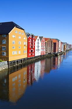 Old fishing warehouses reflected in the River Nidelva, Trondheim, Sor-Trondelag, Norway, Scandinavia, Europe