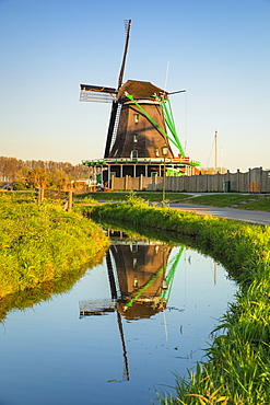 Windmill reflecting in a river, open-air museum, Zaanse Schans, Zaandam, North Holland, Netherlands, Europe