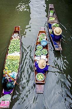 Vendors paddle their boats, Damnoen Saduak Floating Market, Thailand.