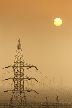 Power pylons stretch into the distance, sun rises through air thick with sand, Suez Canal, Port Said, Egypt, North Africa