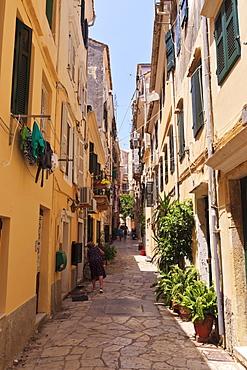 Narrow street with lady sweeping, Old Town, Corfu Town, UNESCO World Heritage Site, Corfu, Ionian Islands, Greek Islands, Greece, Europe
