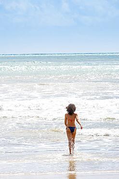 A young woman running into the tropical Atlantic, Morro de Sao Paulo island, Bahia, Brazil, South America