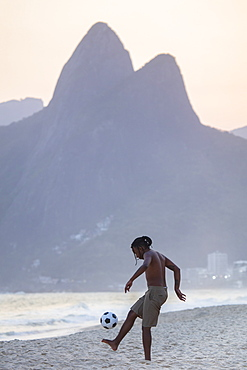 A young black Brazilian playing football on Ipanema beach with the Dois Irmaos mountains in the distance, Rio de Janeiro, Brazil, South America