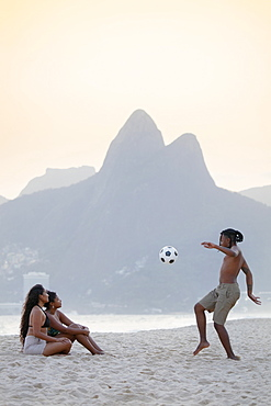 A young black Brazilian playing football with two female friends on Ipanema beach with the Dois Irmaos mountains in the distance, Rio de Janeiro, Brazil, South America