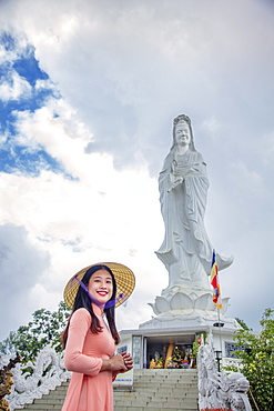 A young Vietnamese woman in a conical hat smiling to camera in front of a statue of Quan Am (Guanyin), Hue, Vietnam, Indochina, Southeast Asia, Asia