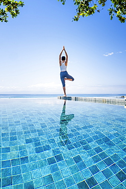 A young woman practising yoga next to an infinity pool, Candidasa, Bali, Indonesia, Southeast Asia, Asia
