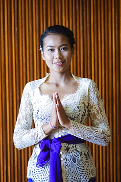 A Balinese woman wearing traditional busana adat temple clothes comprising a white kebaya blouse, a sash and a batik sarong, Bali, Indonesia, Southeast Asia, Asia