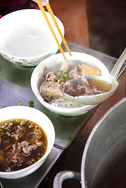 A steaming dish of Bun Bo Hue, the spicy local beef broth or hotpot, in a local restaurant, Hue, Vietnam, Indochina, Southeast Asia, Asia