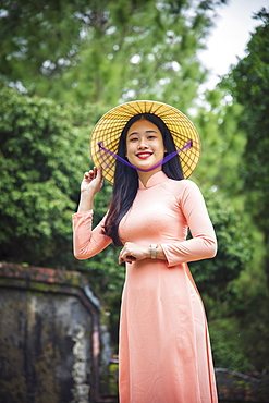 Portrait of a young Vietnamese woman in an Ao Dai dress and conical hat at a Buddhist temple, Hue, Vietnam, Indochina, Southeast Asia, Asia