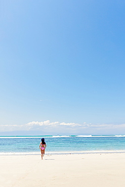 A young woman running into the ocean on a pristine tropical beach, Bali, Indonesia, Southeast Asia, Asia